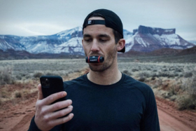 A man looking at phone with Airofit Breathing Trainer in his mouth