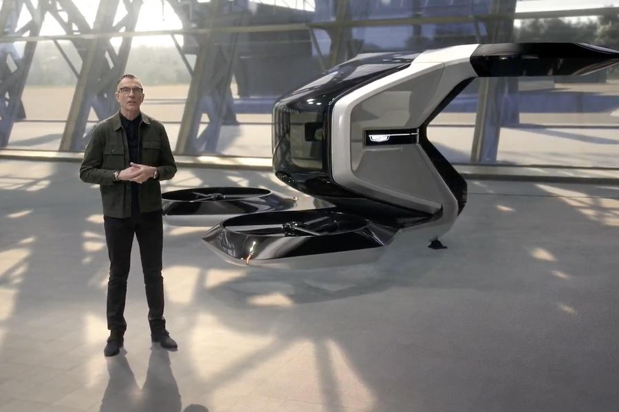 A presenter with GM Cadillac eVTOL air taxi behind him