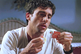 Steve Carrell reading a torn condom packet with a condom in the other hand