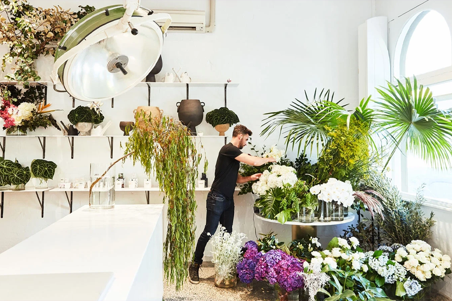 A man taking care of flowers in the nursery