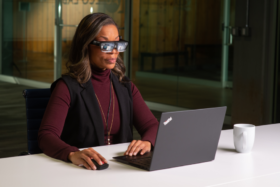 A woman wearing Lenovo's ThinkReality A3 Smart Glasses working on a laptop