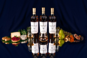 Three Bottles of Macallan whiskey with fruit and sweets around it