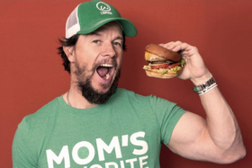 Mark Wahlberg holding a burger near his open mouth