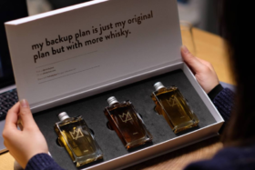 A pair of hands holding a Whisky Loot box