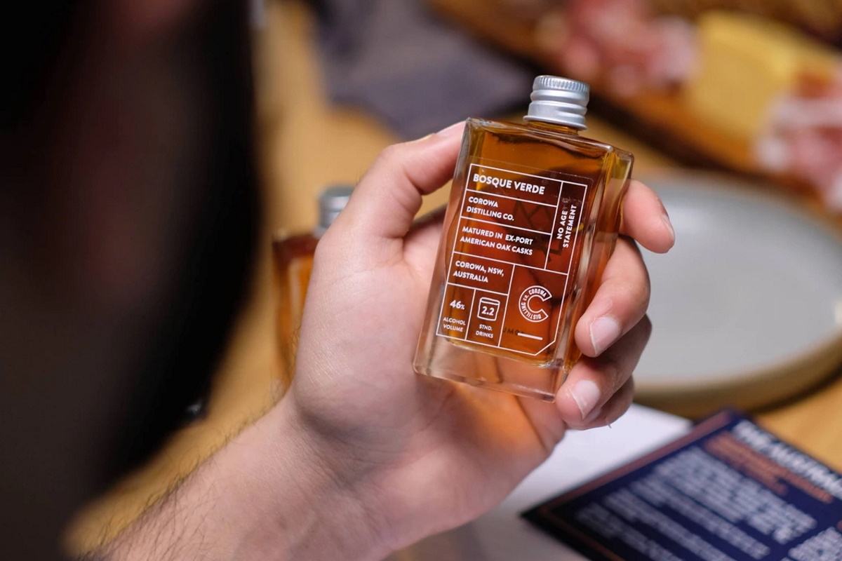 A bottle of whisky in a hand