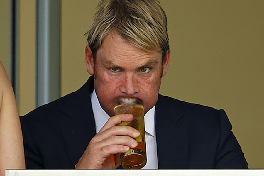 Shane Warne with a beer glass pressed inside his mouth at Royal Ascot