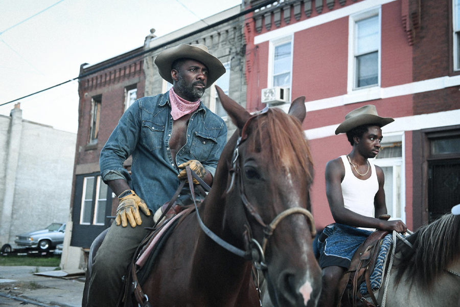 Idris Elba and Caleb McLaughlin riding horses from Concreye Cowboy