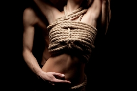 A woman with rope tied around her chest. Man holding the woman's stomach from behind.