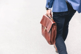 A man with a leather office bag