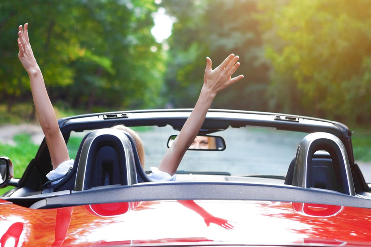 A person with hands thrown in air on the front seat of a convertible car