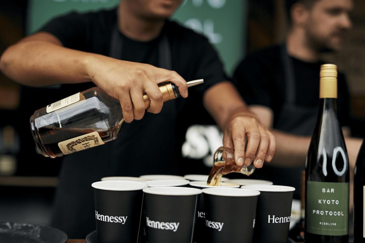 A barista pouring wine in glasses