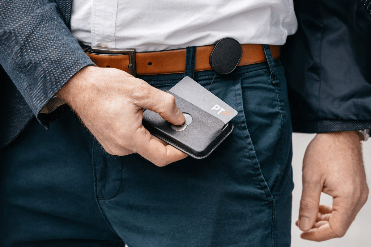 A man pushing out a card from Orbitkey ID Card Holder attached to his belt