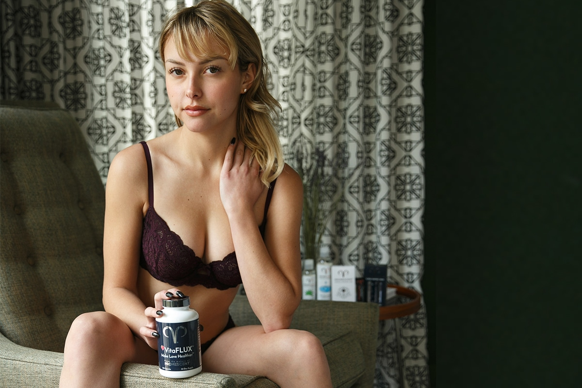 A model in lingerie with a bottle of VitaFLUX