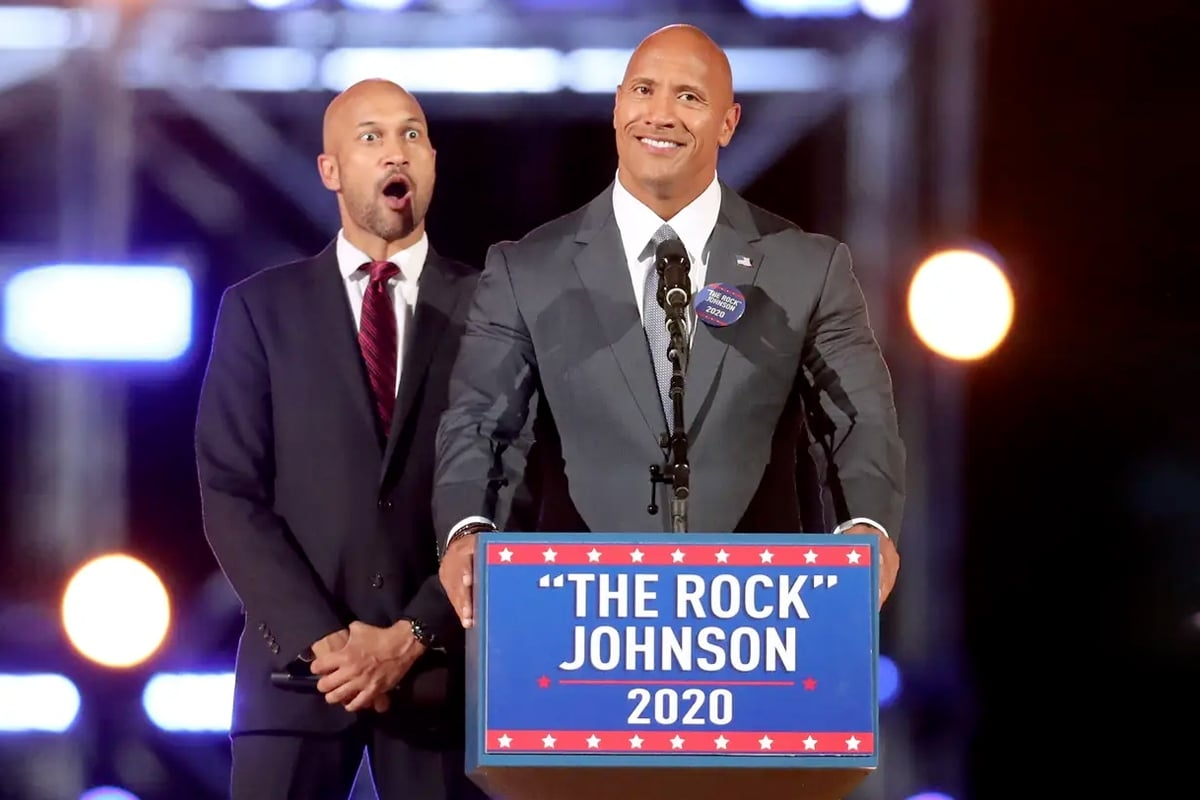 Rock in suit standing at a podium with The Rock Johnson 2020 sticker