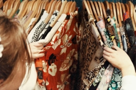woman browsing through vintage clothing thrift