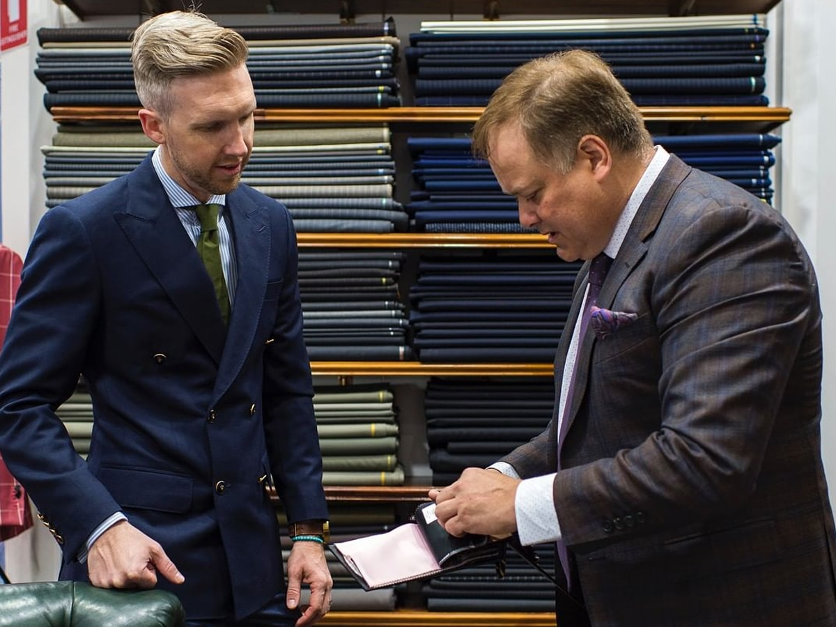 tailor and customer in suit shop