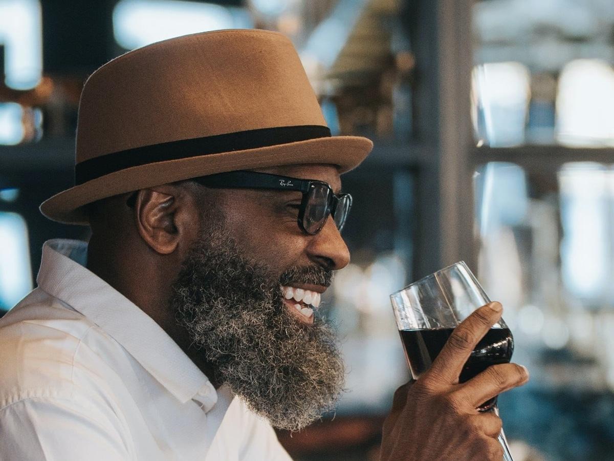 man in hat drinking wine