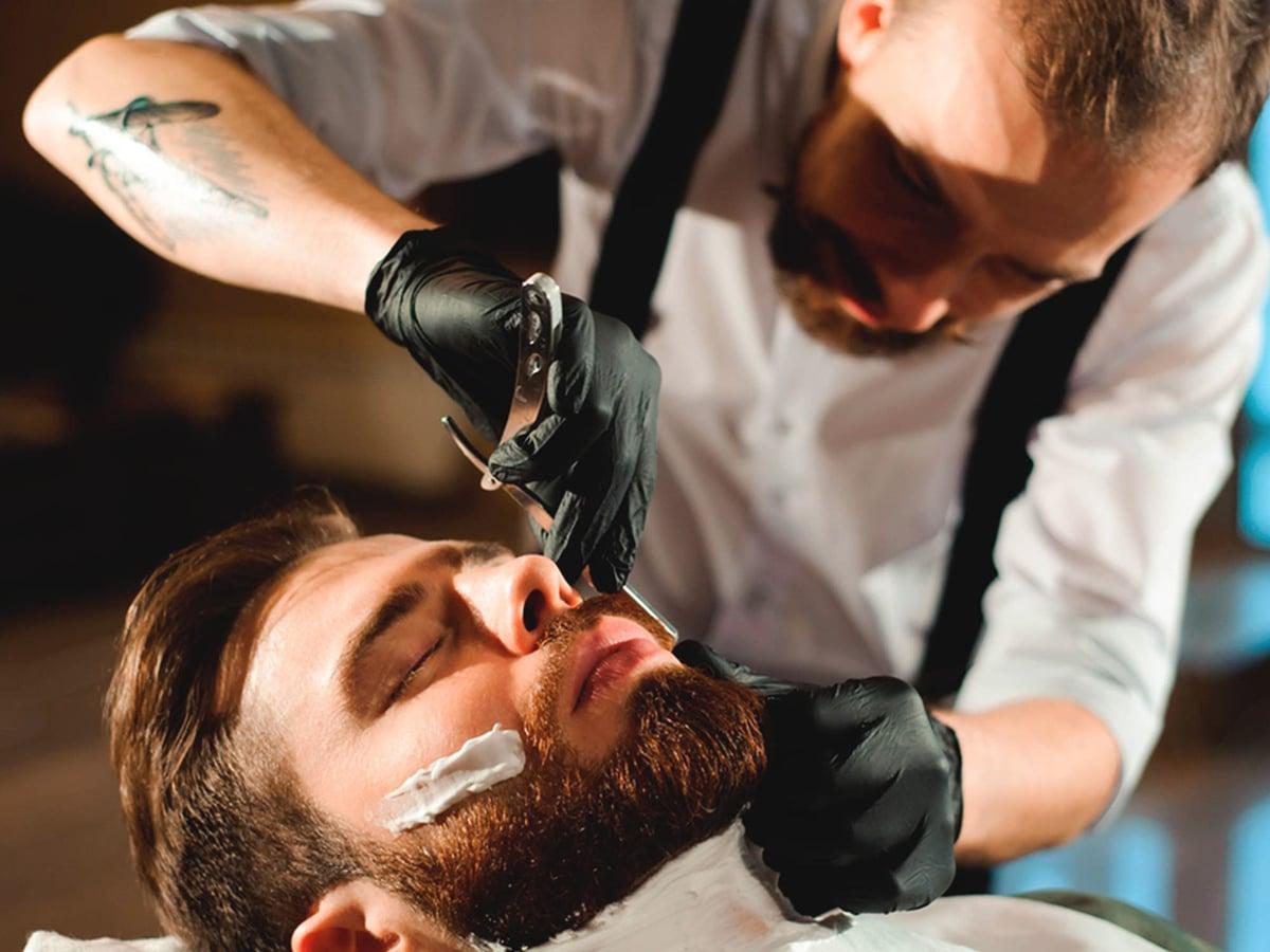 Stylish Barber Grooming a Man`s Beard