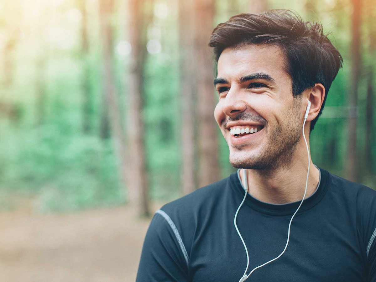 happy man with earphones in the forest