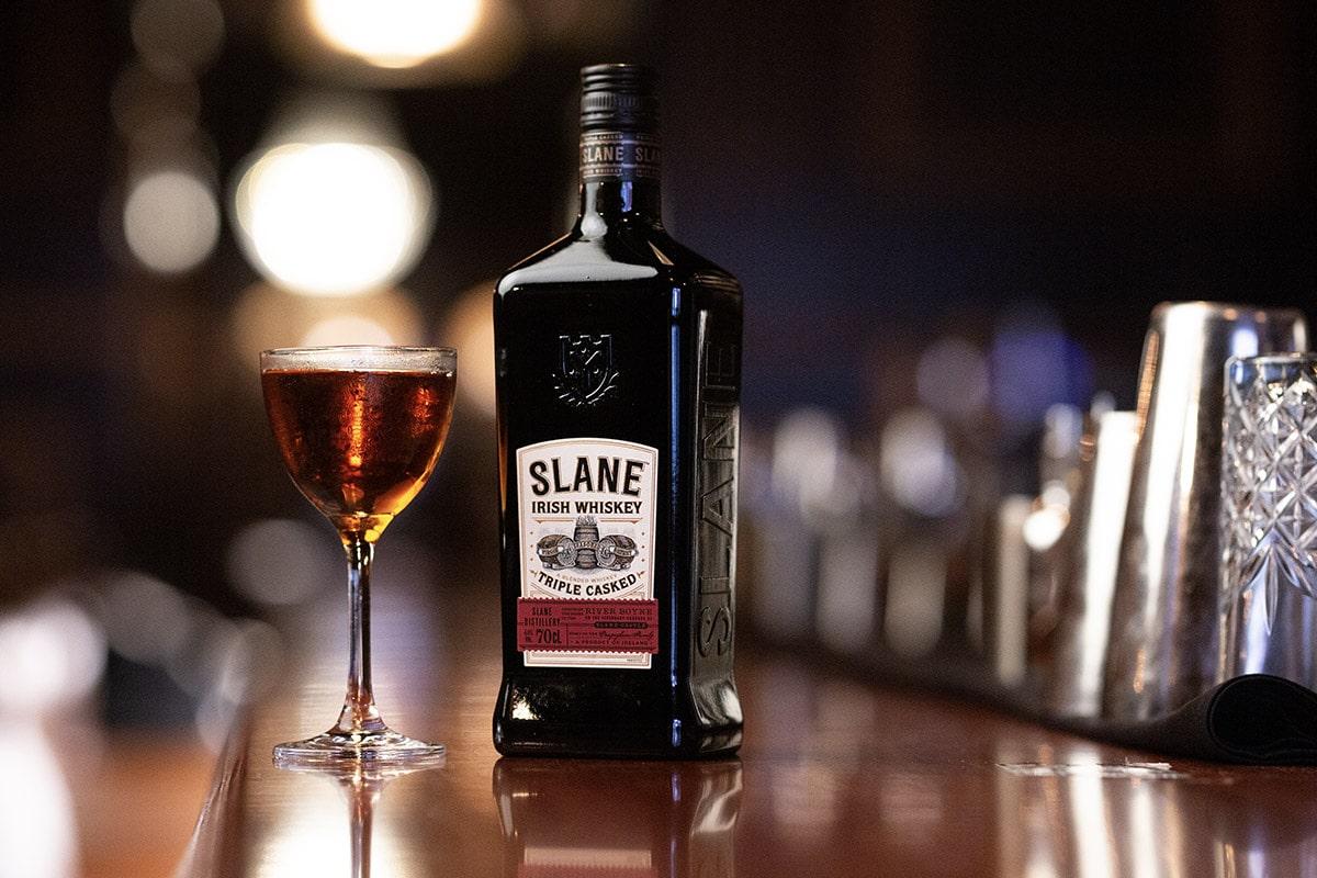 Bottle of Slane Irish whiskey next to a filled glass