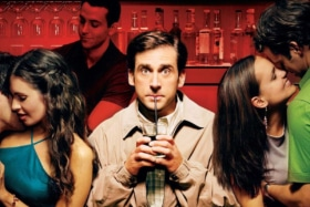 Steve Carell drinking with a strawat a bar as two couples make out on his sides in a poster from The 40-year-old virgin