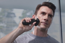 A man shaving with a Panasonic rechargeable shaver
