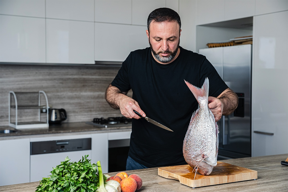 Chef Rantissi holding a knife with a fish in the other hand