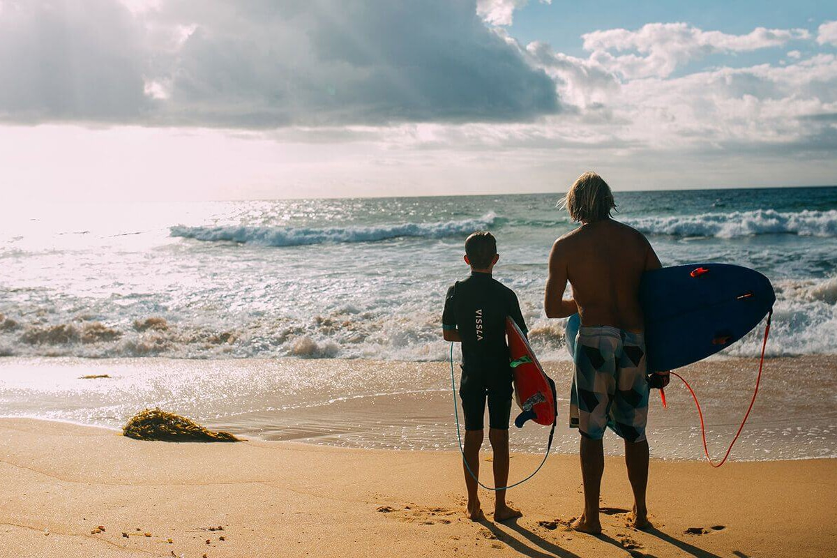 two surfers standing on the shelly beach