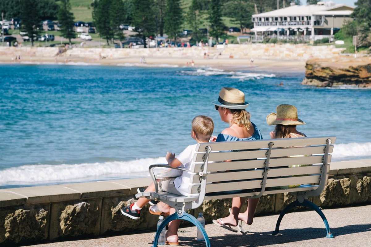 woman with two kids sitting on a bench at terrigal beach