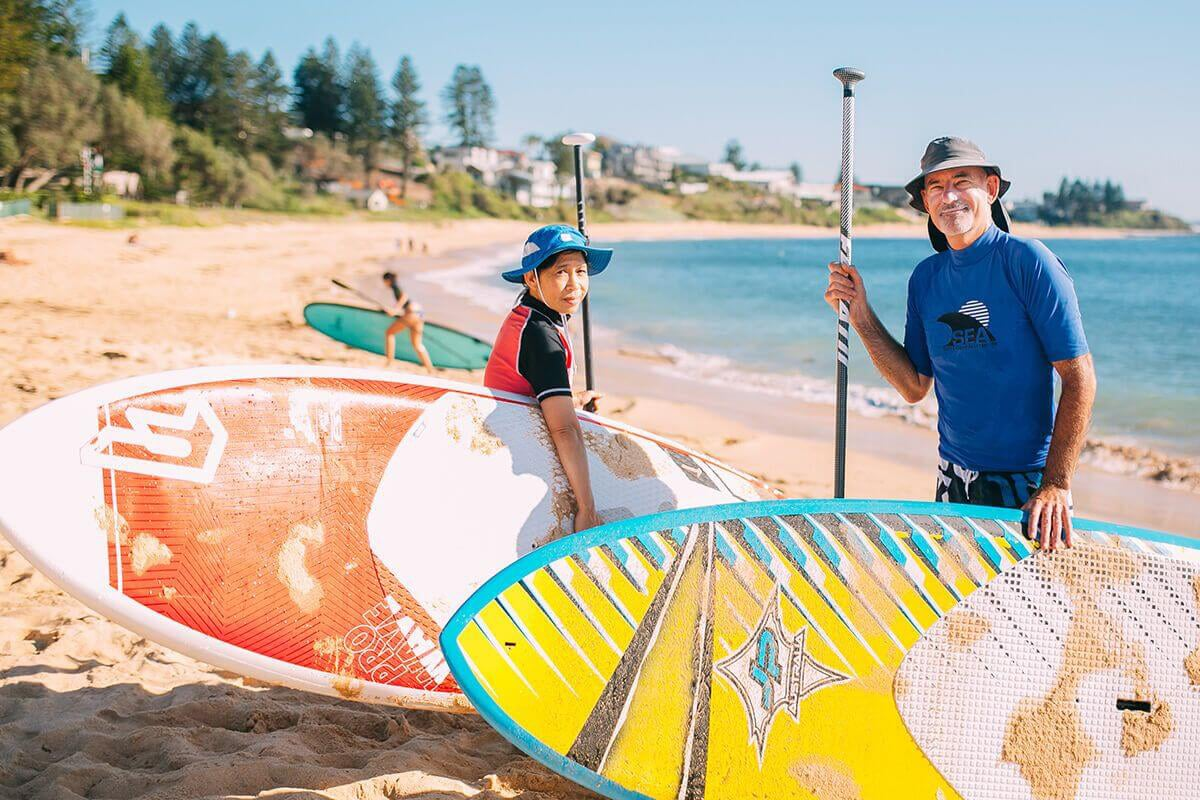 people with paddle boards standing on the toowoon bay beach