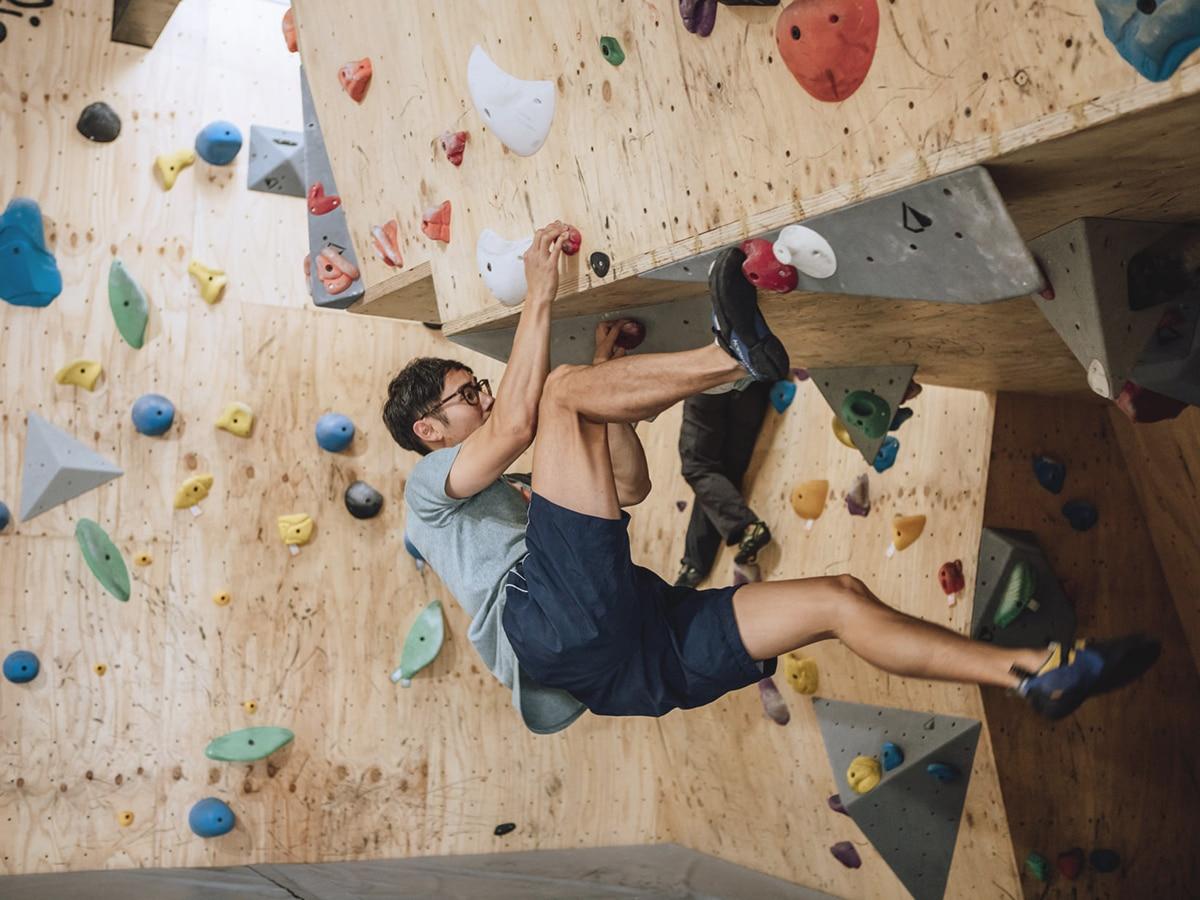 man climbing in boulder project rock climbing gym