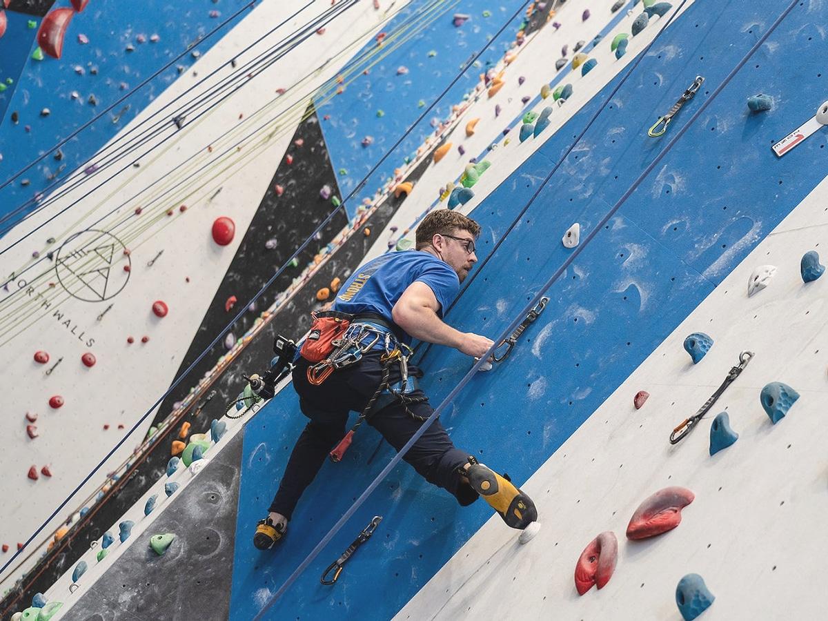 man climbing wall in north walls rock climbing gym