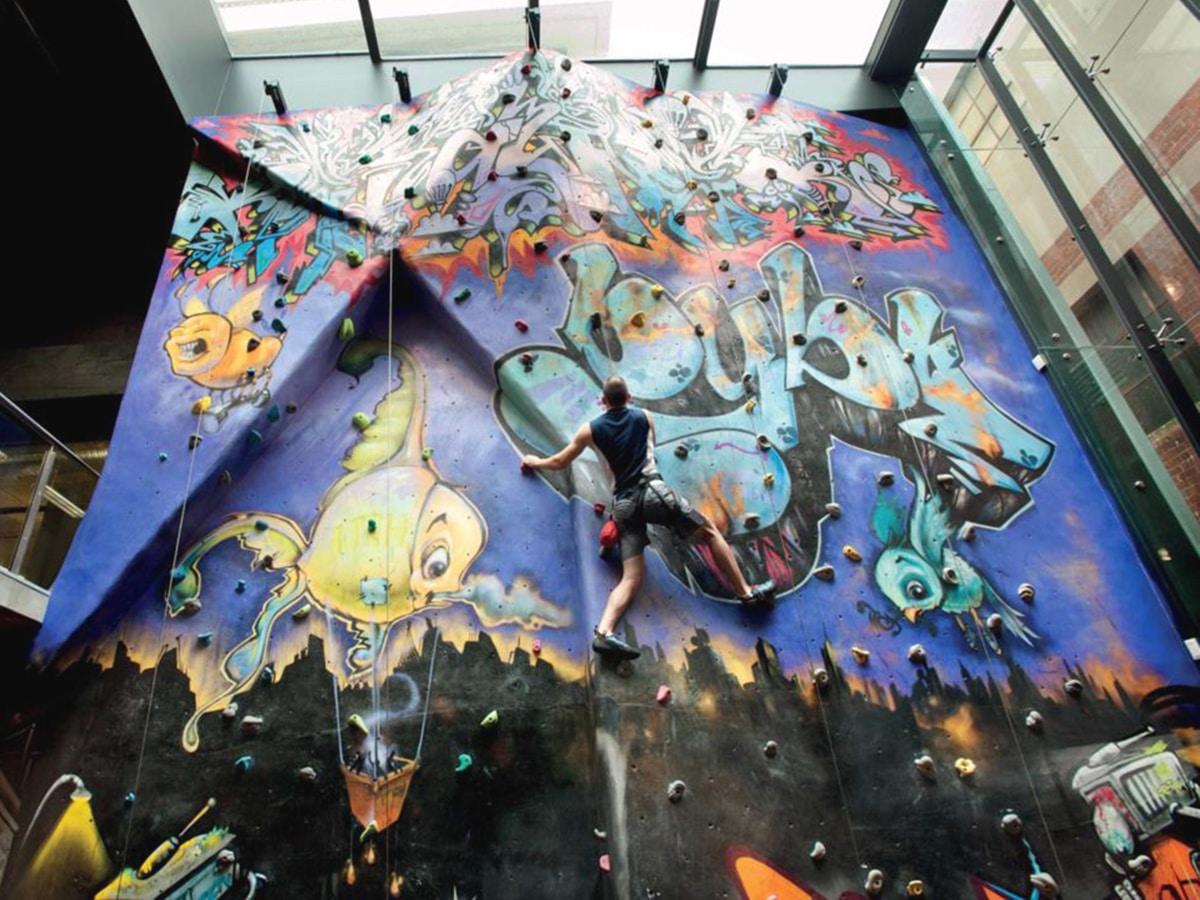 man climbing wall in virgin active rock climbing gym