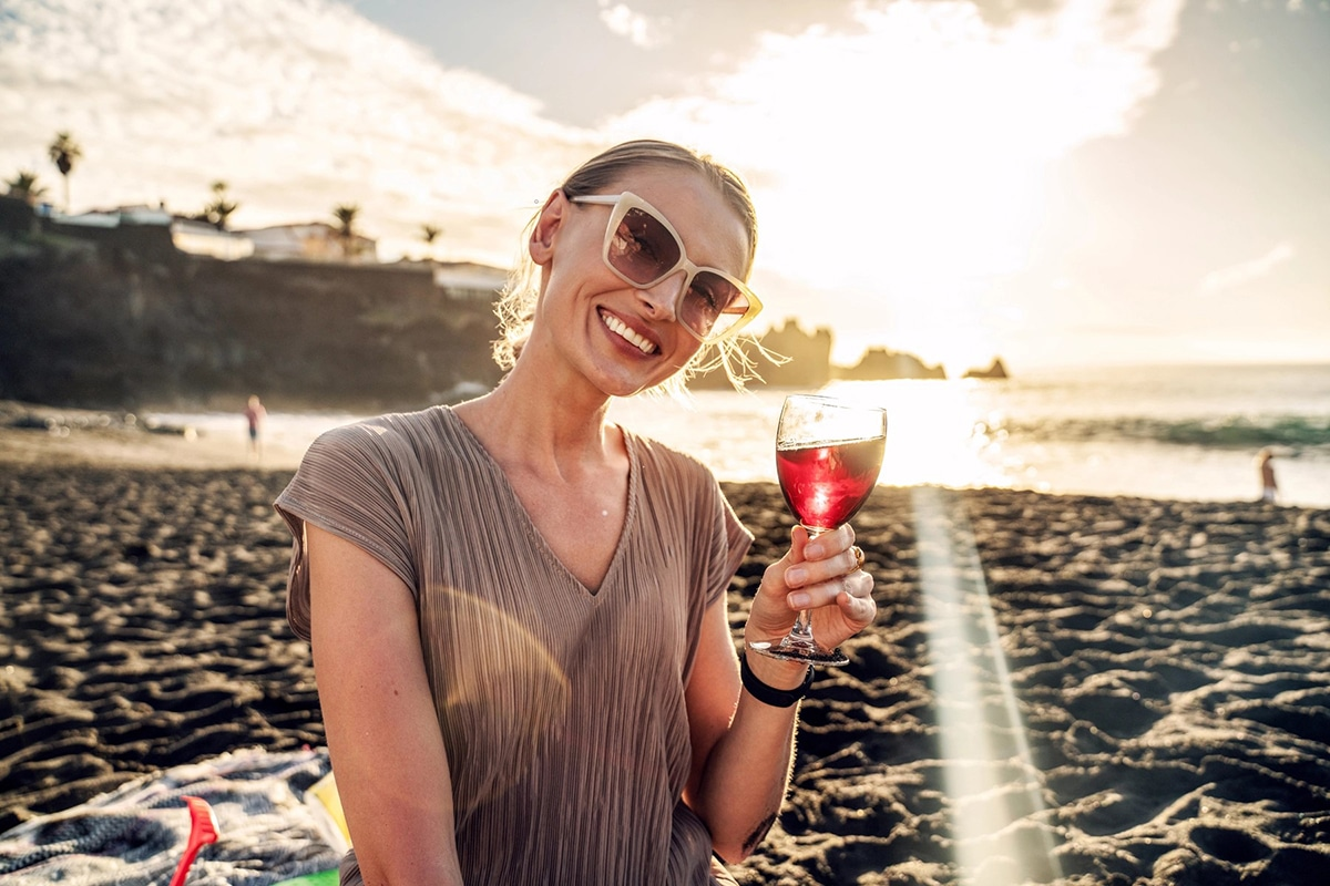 young woman is sitting on sea beach with wineglass of wine