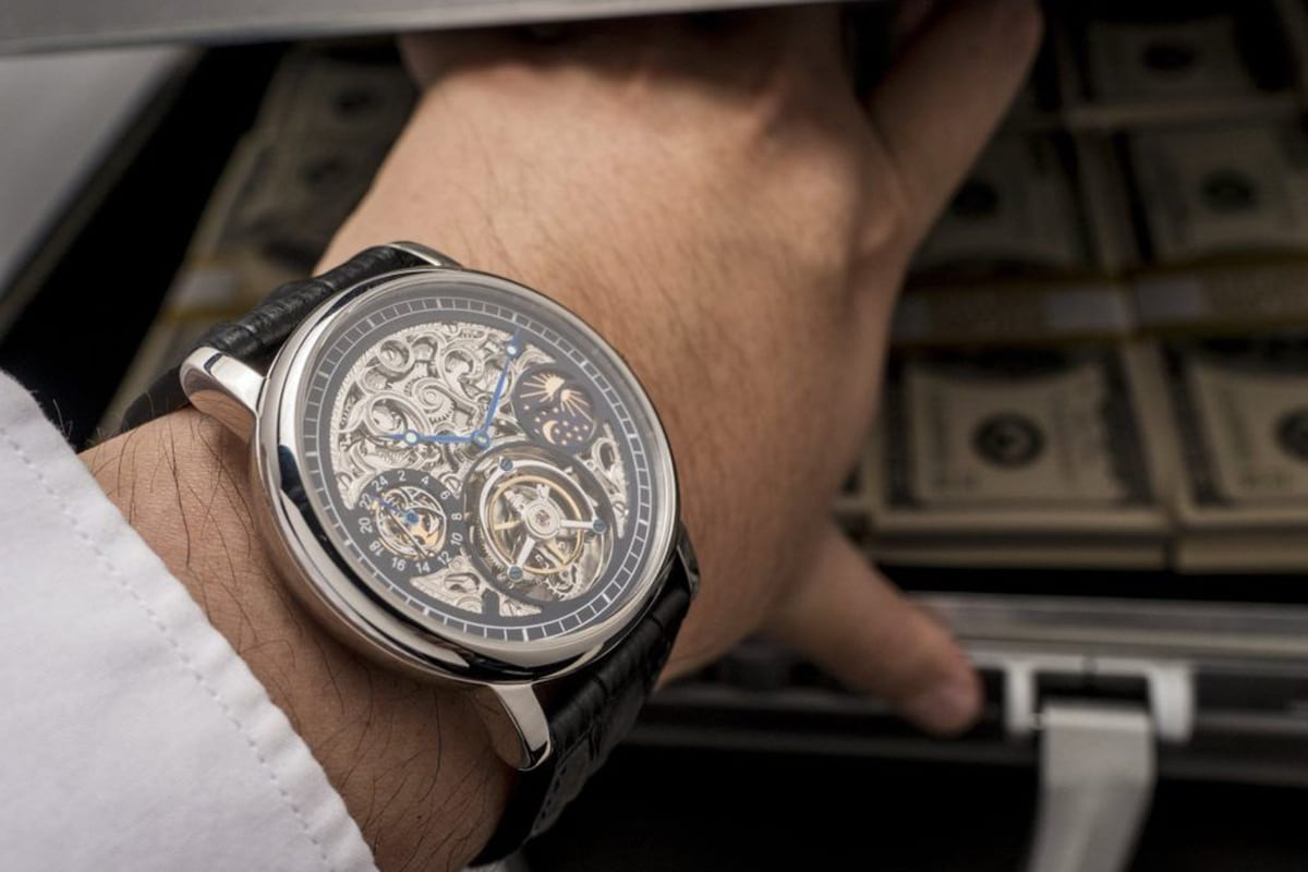 tourbillon watch on man's hand in front of money