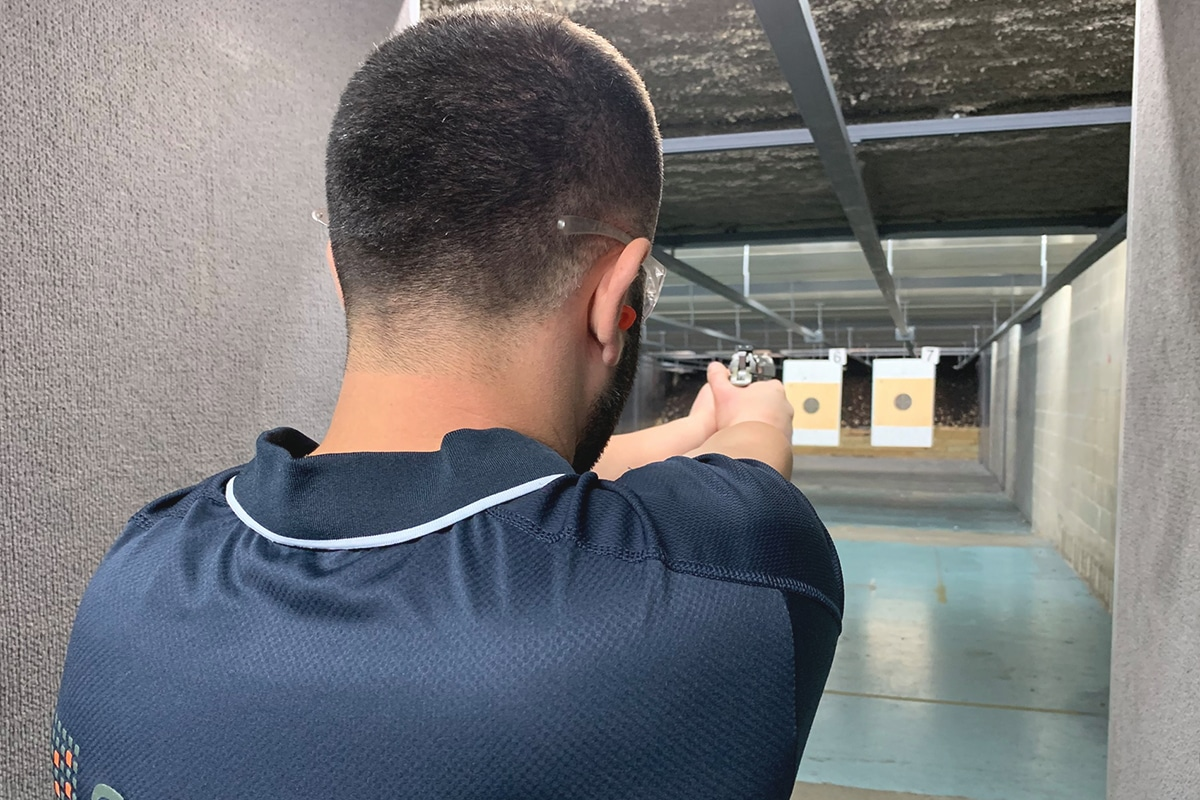 man aiming gun at target in st marys indoor shooting centre