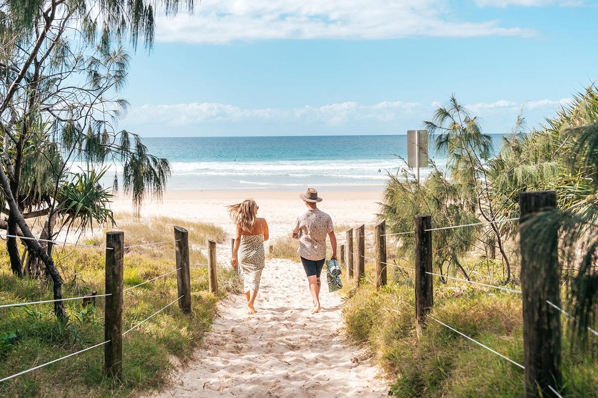 Couple Walking Down The Coolum Beach