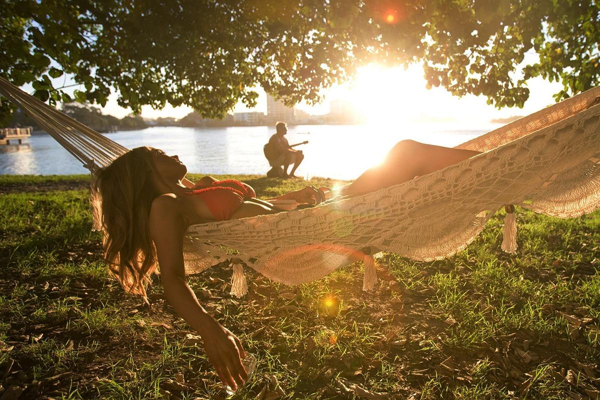 Woman Relaxing In Hammock On cotton tree beach