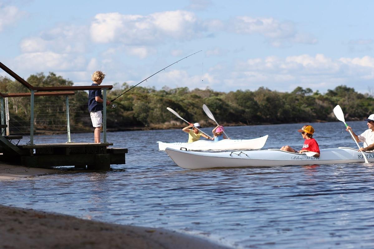Kid fishing and People Swimming In Kayaks on lake currimundi