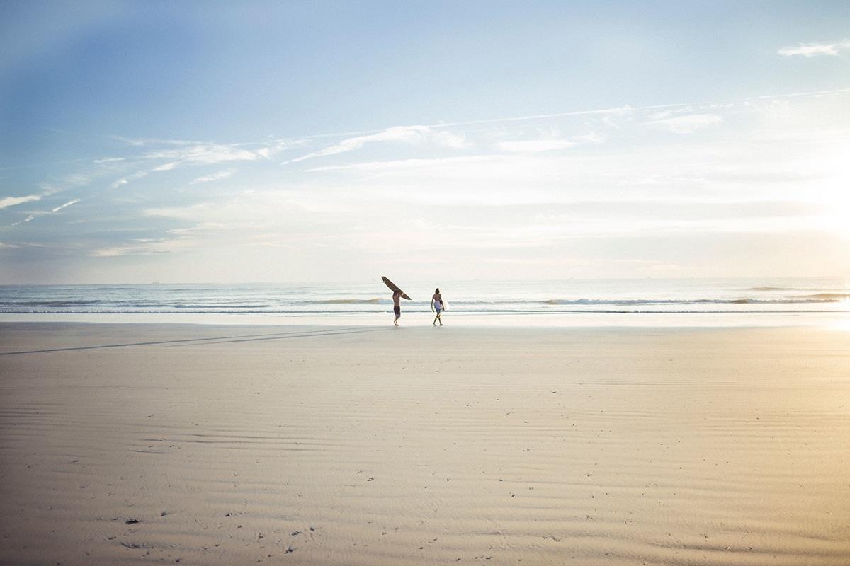 two surfers walking on wurtulla beach