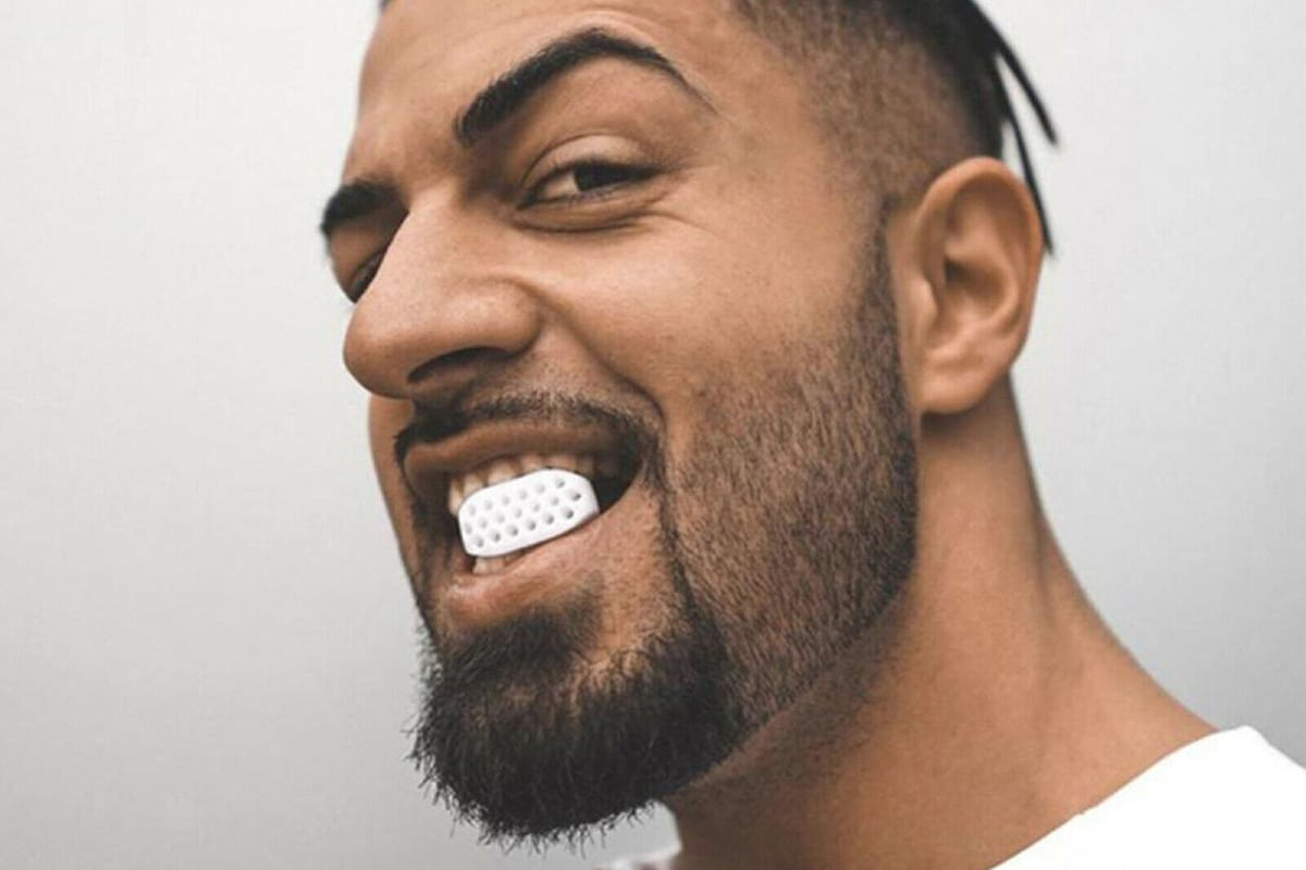 man with Jawline exerciser in teeth