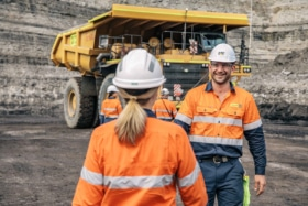 mining engineers in front of a big yellow mining truck