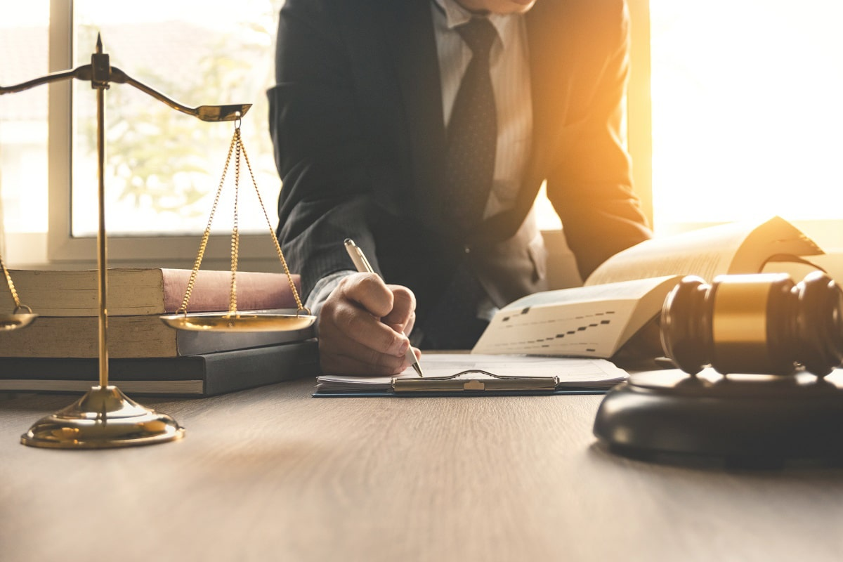 legal professional taking notes near scales of justice
