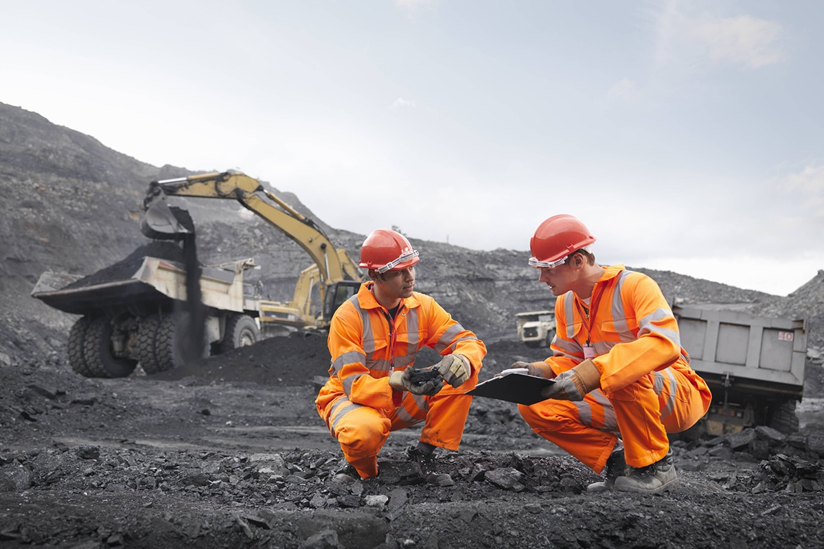 mining engineers talking in front of excavator