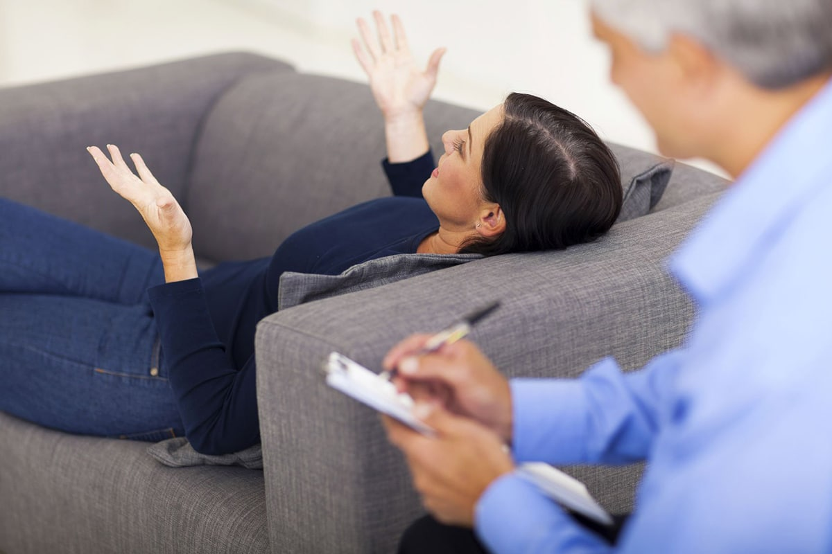 patient woman lying on sofa and talking with psychiatrist