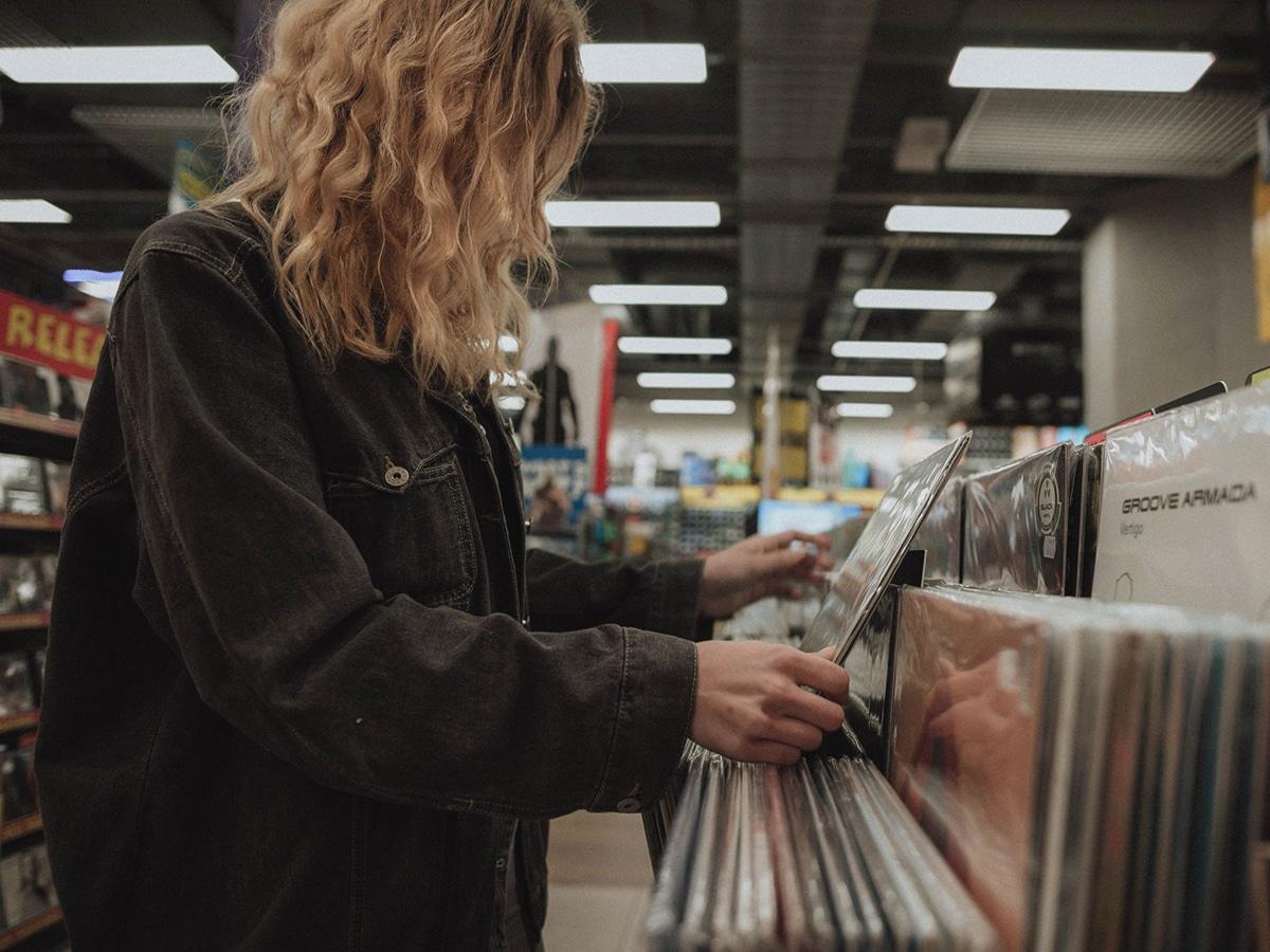 young woman choosing vintage vinyl record at papa disquo records