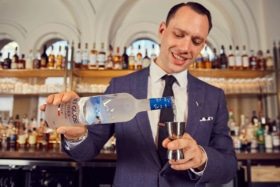smiling man pouring grey goose vodka