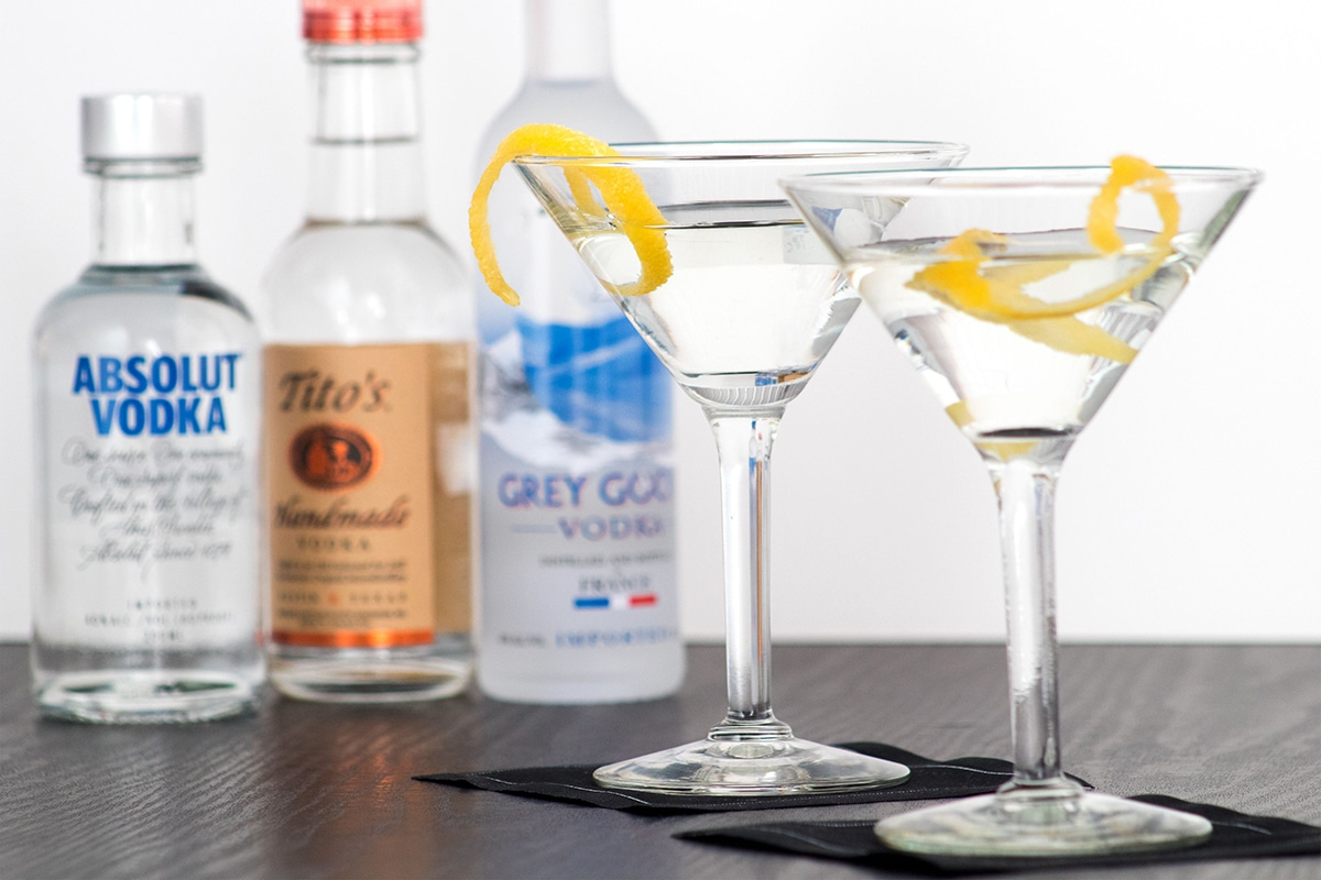 glasses of vodka with lemon in front of bottle of absolut vodka and grey goose vodka