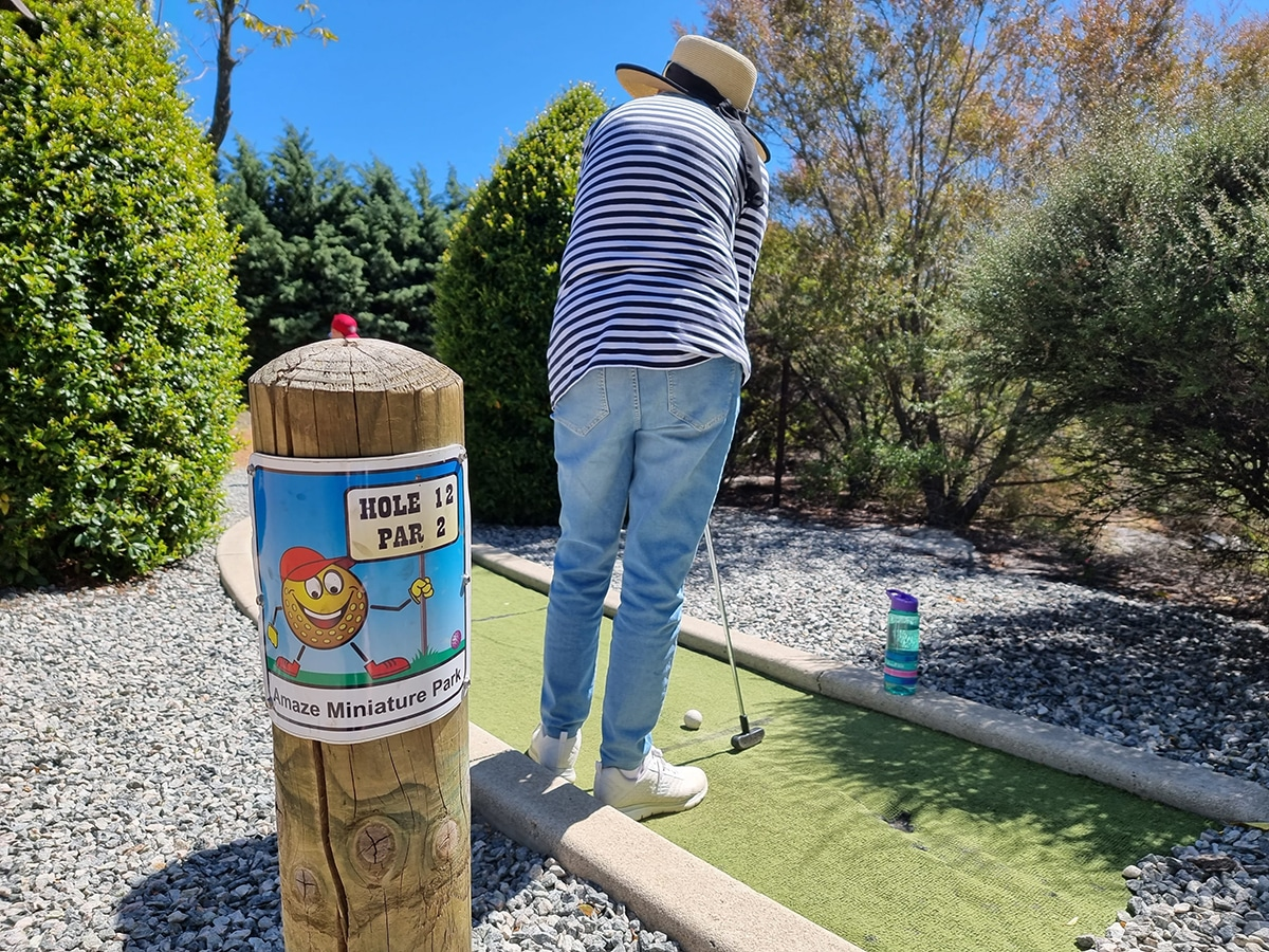 woman playing mini golf at amaze miniature park