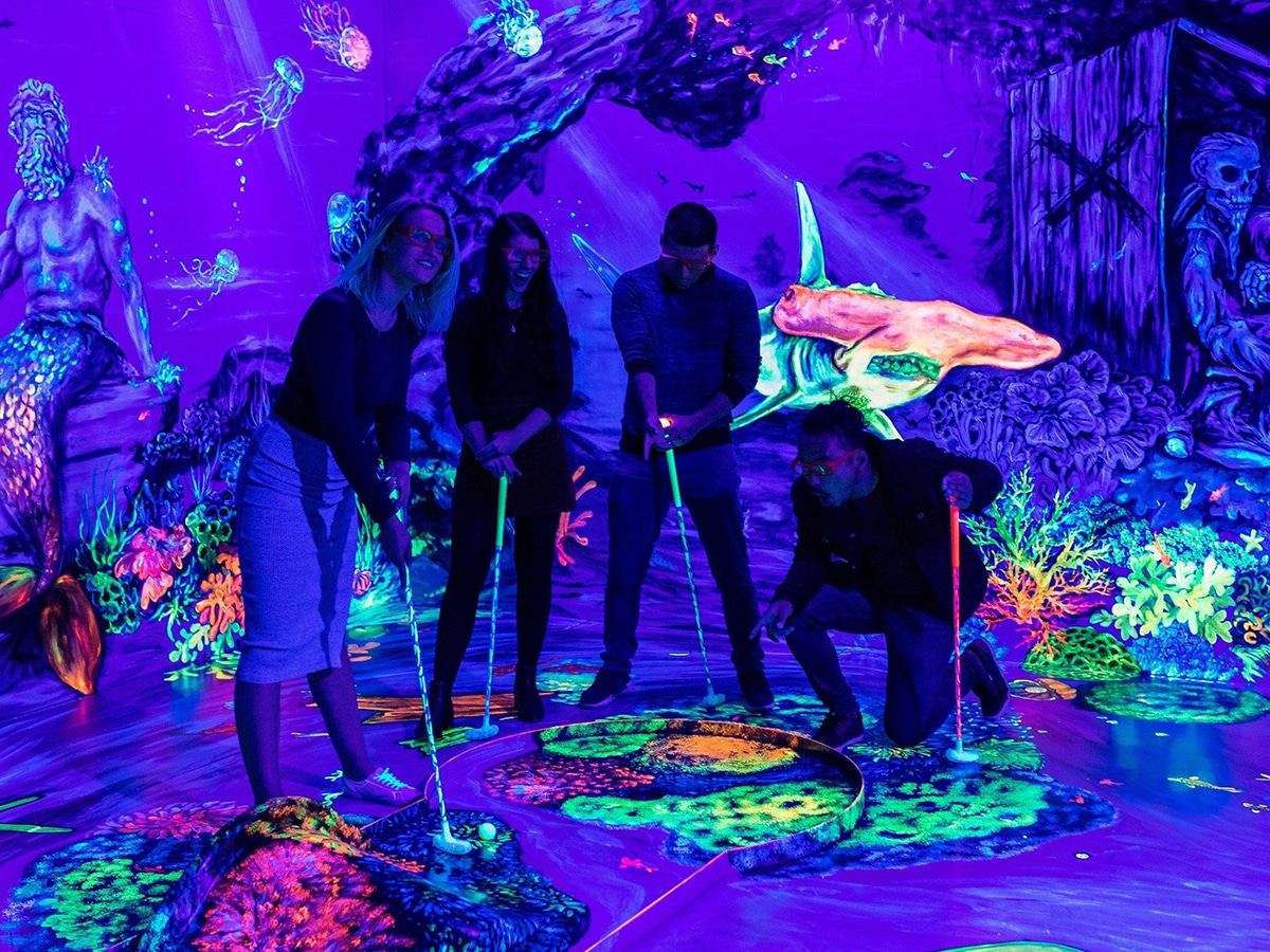 group of people playing minigolf at glowing rooms
